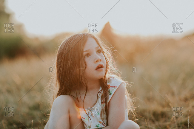 Portrait of a little girl sitting in a field at sunset