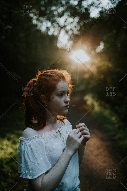 Ginger girl wearing off-shoulder blouse at sunset