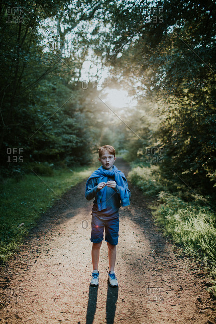 Young boy standing on a beautiful forest path