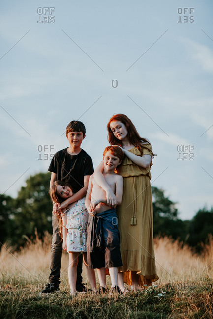 Four siblings posing in a sundrenched field