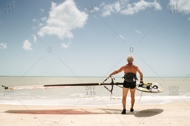 Man carrying wind surfing board to the water