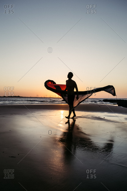 Man walking on beach with a kite surfing scale