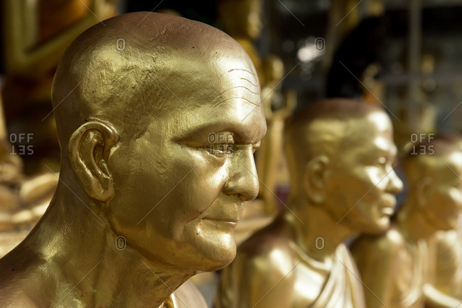 Side view of row of golden shiny statues of monks