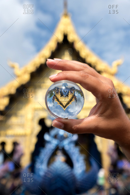 Crop hand of tourist holding glass ball with upside reflection of ancient temple in Thailand