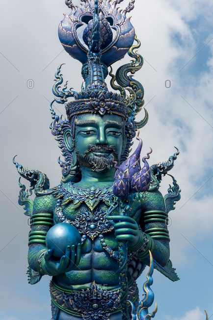 From below shot of colorful ancient statue of oriental god with ornamental design outdoors, Thailand
