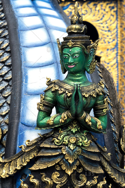 Design of ancient Buddha statue in green and gold colors, Chiang Rai