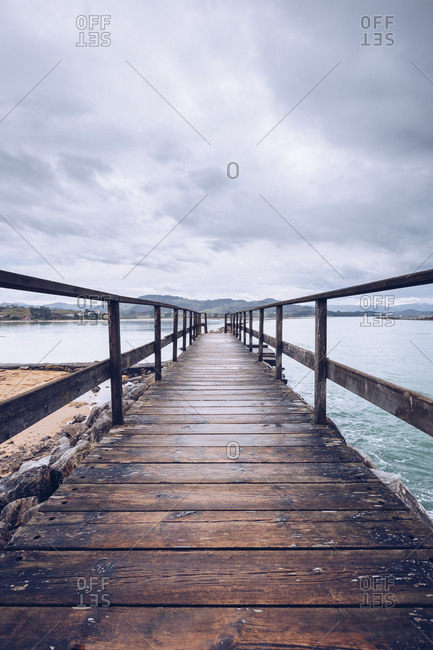 Weathered umber pier located on shore near surface of calm water on cloudy day in Asturias, Spain