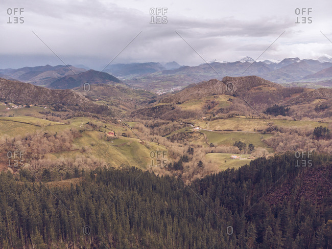 Picturesque drone view of majestic mountain ridge and hilly terrain on cloudy day in Asturias, Spain