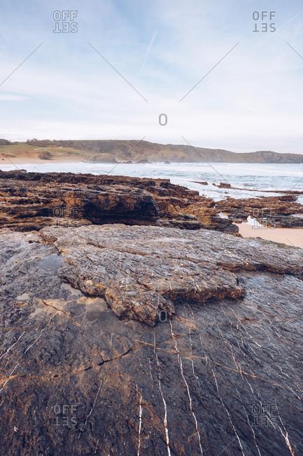 Calm sea water near small bay near stony coast on sunny day in Asturias, Spain