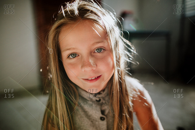 Portrait of a smiling girl with blond hair and blue eyes
