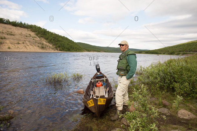 August 30, 2017: Fisher tourist with wooden boat by the river bank, Utsjoki, Lapland