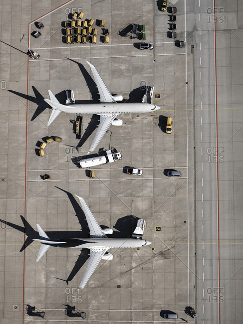 Aerial view commercial airplanes being serviced on tarmac at airport