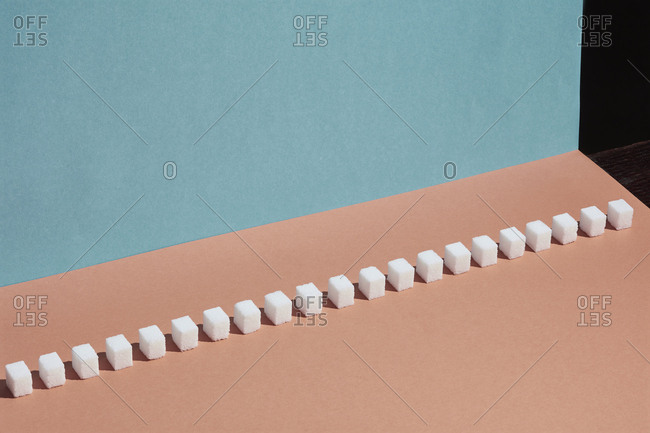 Sugar cubes in a row on peach background