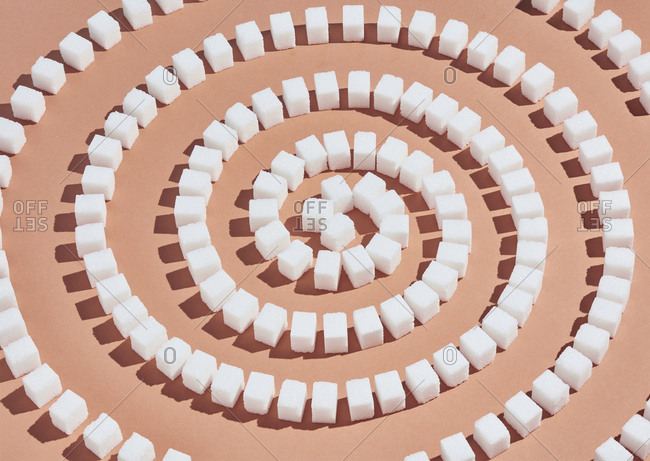 Sugar cubes forming spiral pattern on peach background