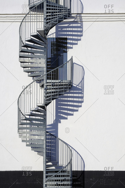 Spiral staircase and door along sunny wall
