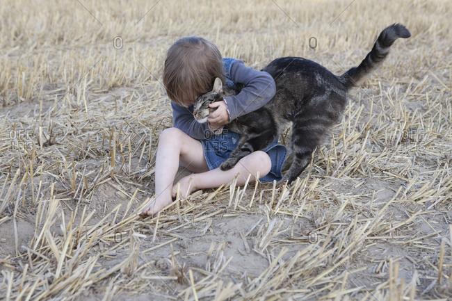 Affectionate girl hugging cat