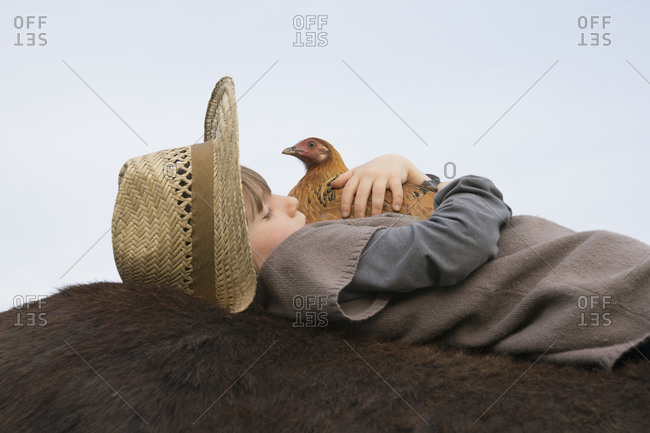 Girl hugging chicken, laying on horse