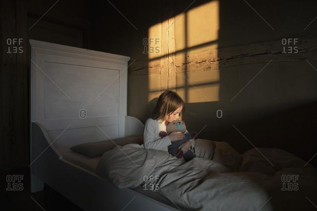 Girl hugging teddy bear in bed