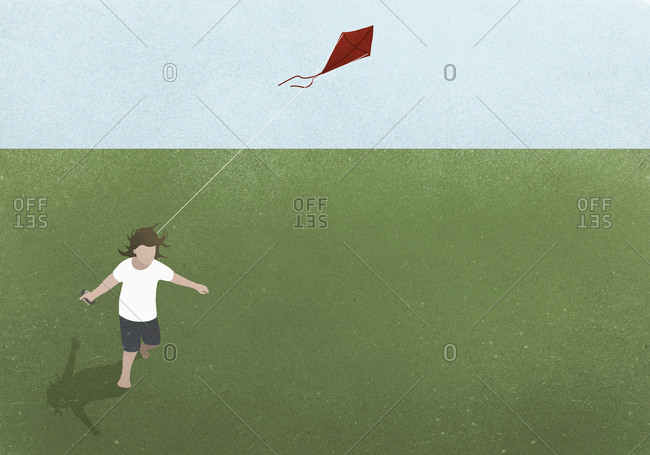 Girl running with kite in grassy field