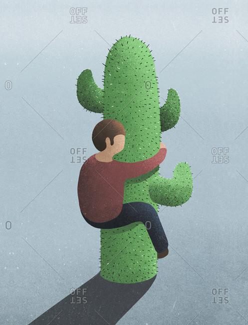 Man hugging prickly cactus