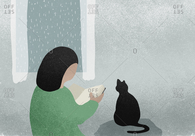 Woman with cat reading book next to rainy window