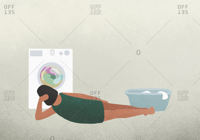 Woman laying and watching clothes drying in dryer