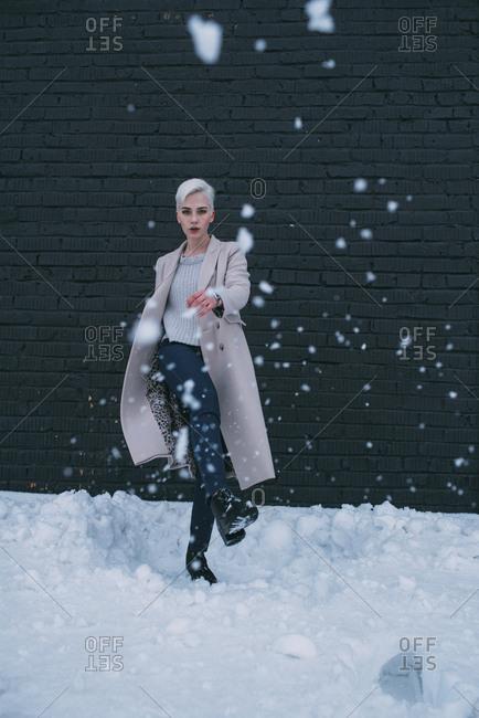 Portrait young woman kicking snow