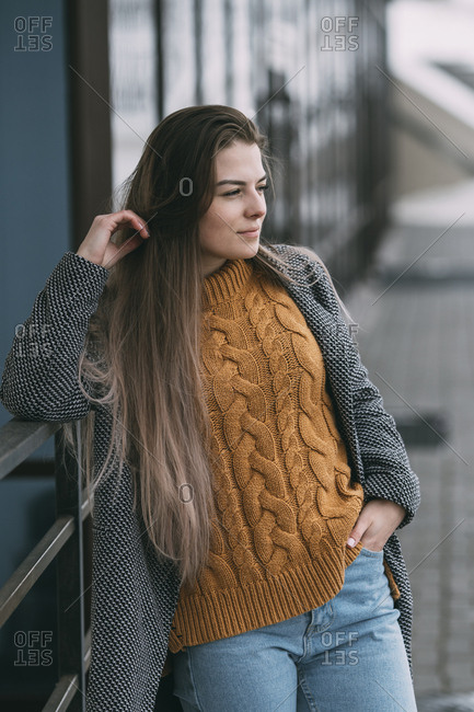 Young woman leaning against railing, looking away