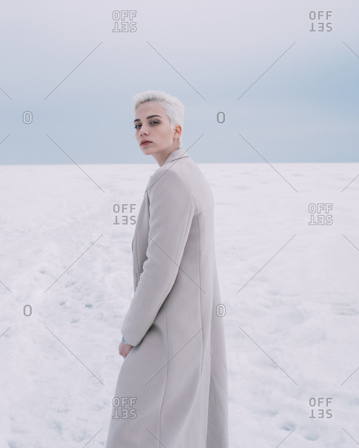 Portrait confident young woman walking in snow