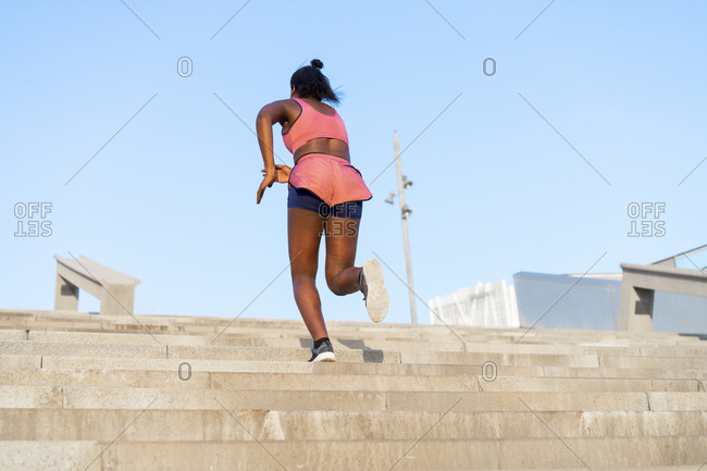 Young woman during workout on stairs- climbing stairs
