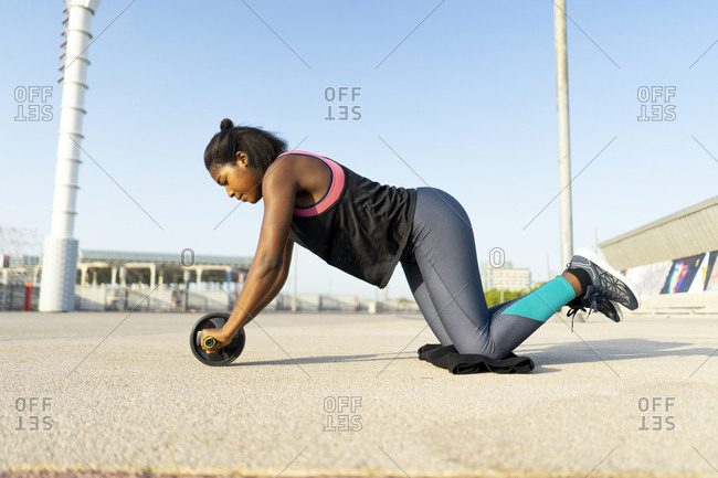 young sportive woman training with an ab wheel