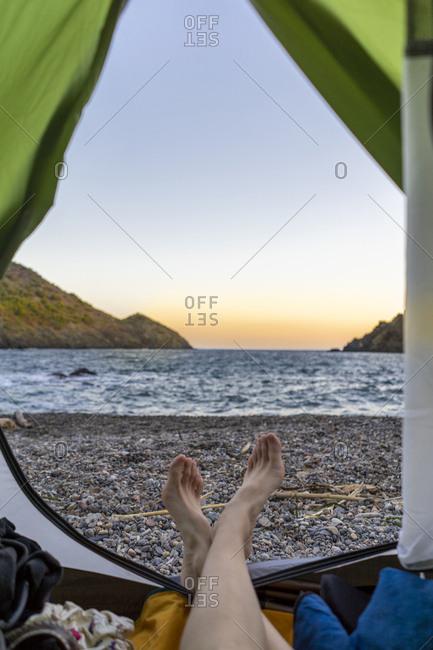 Spain- Catalonia- Costa Brava- woman lying barefoot in tent