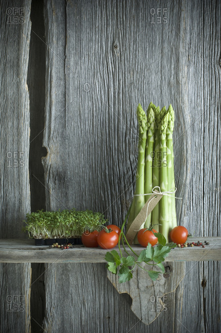 Bundle of green asparagus- tomato- cress- parsley and mixed pepper on wood