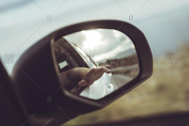 Greece- Crete- hand in rear-view mirror of a car