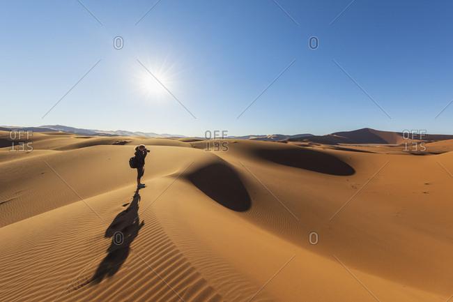 Africa- Namibia- Namib desert- Naukluft National Park- female photographer on sand dune against the sun