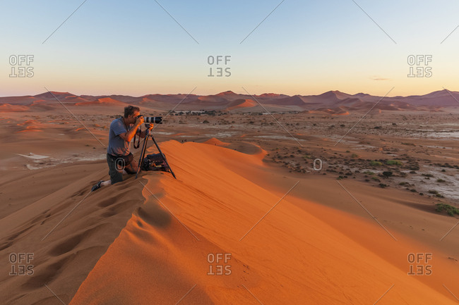 Africa- Namibia- Namib desert- Naukluft National Park- photographer on sand dune at sunrise