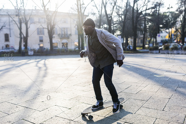 Young man skateboarding on an urban square