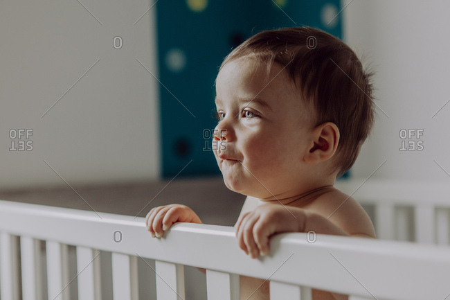 Baby boy standing in his cot