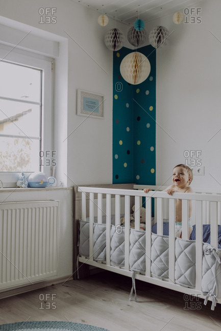 Baby boy standing in his cot- laughing