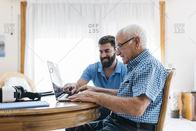 Adult grandson teaching his grandfather to use laptop