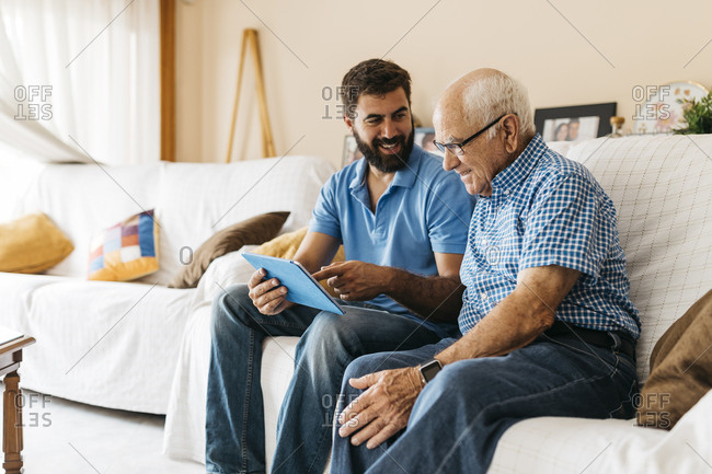 Adult grandson teaching his grandfather to use tablet