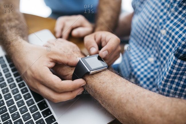 Adult grandson teaching his grandfather to use smart watch- close-up