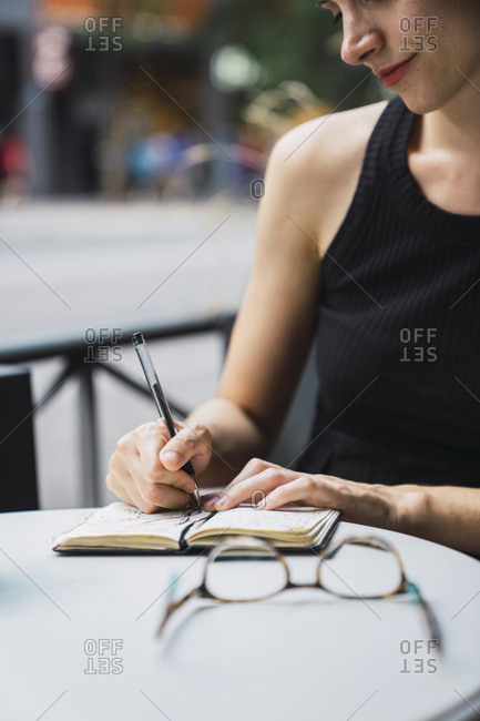 Young woman sitting in coffee shop- brainstorming- writing notes in notebook