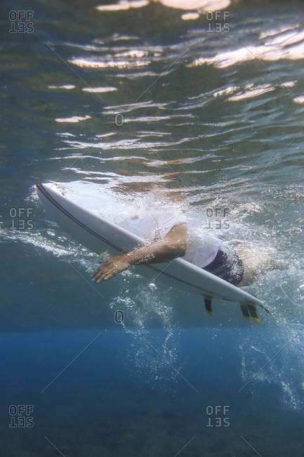 Maldives- Indian Ocean- surfer lying on surfboard- underwater shot
