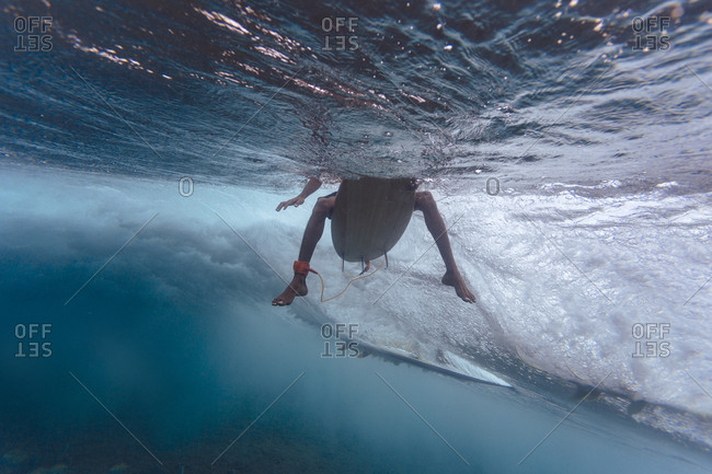 Maldives- Indian Ocean- surfer sitting on surfboard- underwater shot