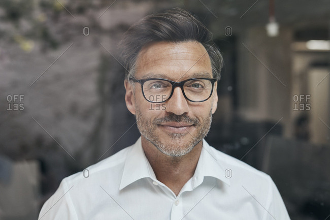 Portrait of man with stubble behind windowpane wearing white shirt and glasses