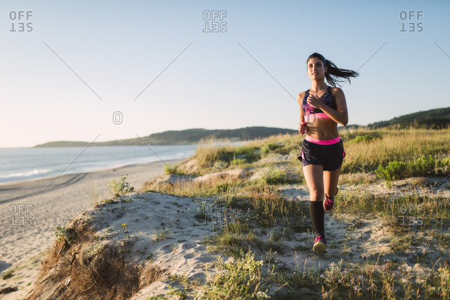 Young sportswoman training on the coast- jogging