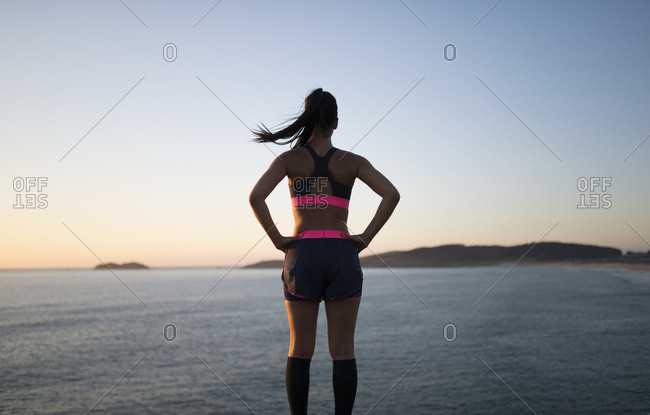 Sportive woman watching sunset- rear view