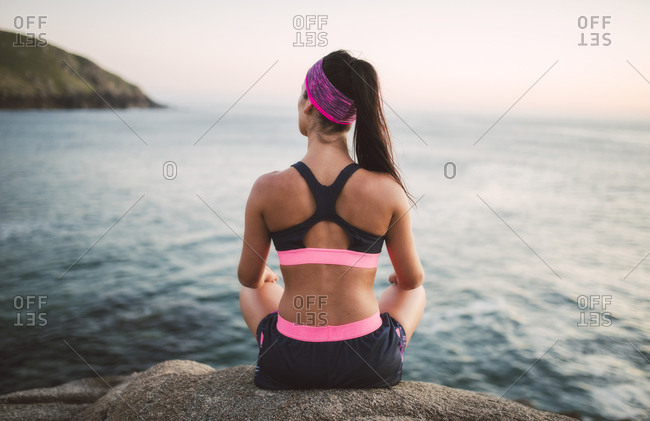 Sportive woman sitting on rocks- facing the sea in the evening- rear view
