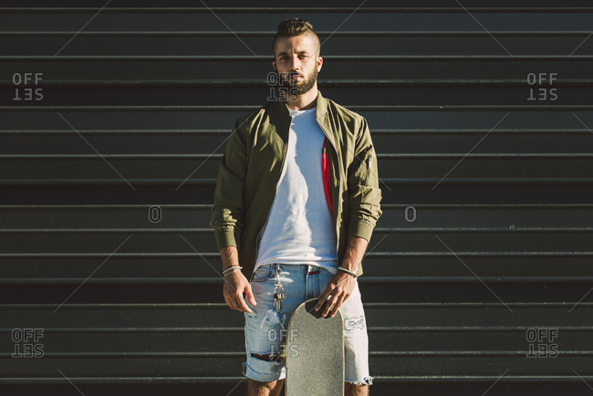 Portrait of young man with skateboard